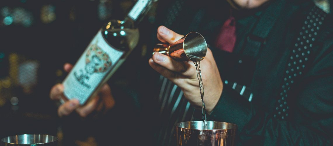 bartender using a jigger to measure tequila for a drink
